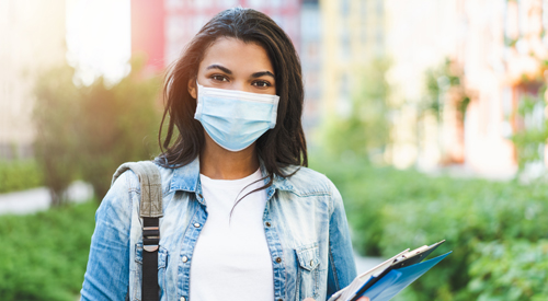 Young black woman outdoors, wearing a surgical facemask and carrying books and files.